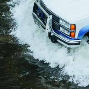 A car drives through a flooded street
